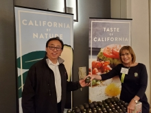 Connie Stukenberg shows John Fujii (Gelson's) beautiful, fresh California avocados with California avocado-branded banners as a backdrop.