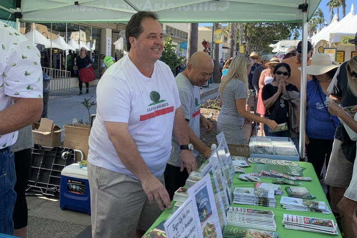 CAC Board Member Gary Caloroso, California avocado grower Trish Shade and David Cruz handing out recipe booklets, avocado cutters and other materials to the festival attendees.